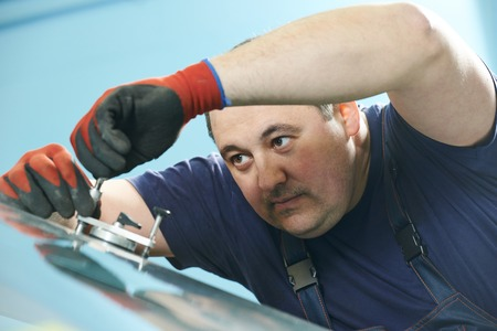 Technician squeezing filler into auto glass crack